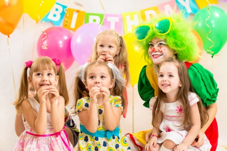 jolly children group and clown on birthday party photo