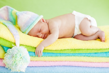 newborn baby girl sleeping on color towels photo