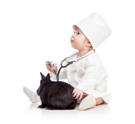 Baby playing doctor with pet bunny photo