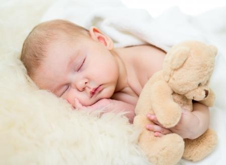teddy bear: beb� reci�n nacido que duerme con el juguete de felpa Foto de archivo