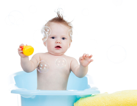 baby bath: baby boy taking bath in tub and playing with soap bubble