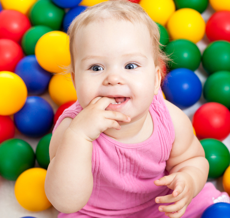 Portrait of a smiling infant sitting among colorful balls photo