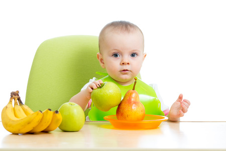 solid food: baby girl eating healthy solid food fruits