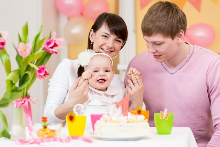 first birthday: young family celebrating first birthday of baby girl