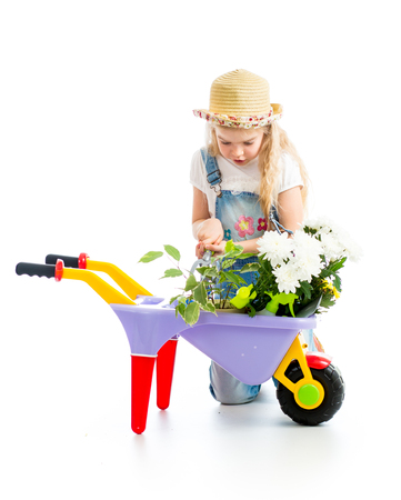 kid girl with potted flowers and gardening equipment isolated photo