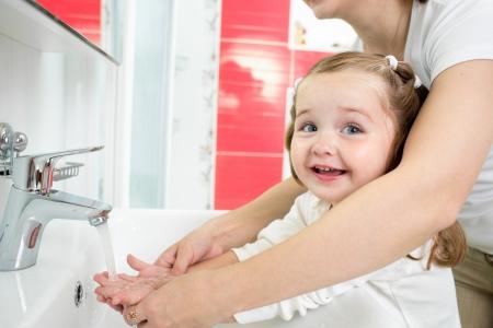 Kid washing hands in bathroom photo