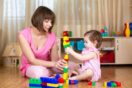 Happy mother and kid play toys at home interior photo