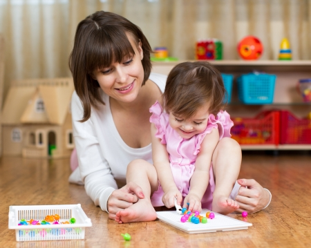 mom and her kid girl play toys in children room photo