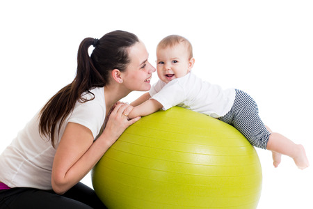 mother playing with baby on fit ball photo
