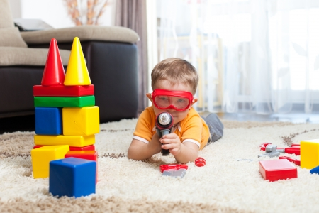 imagining: kid playing with building blocks and imagining himself a hero Stock Photo