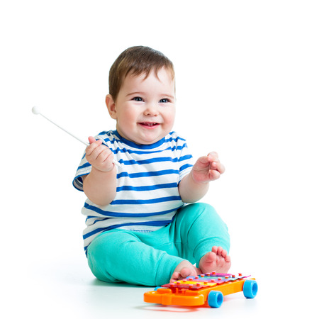 funny baby boy playing with musical toys photo