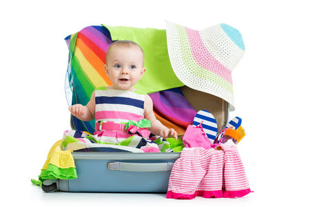 Kid girl sitting in suitcase with clothes for vacation travel photo