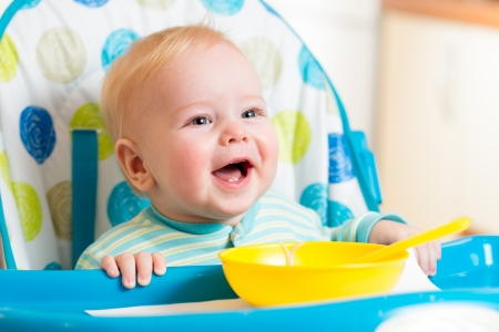 feed up: smiling baby eating food on kitchen Stock Photo