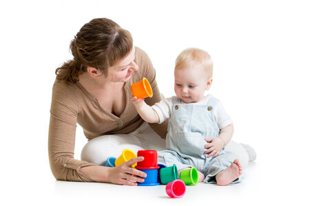 Baby boy and mother play together with toys photo