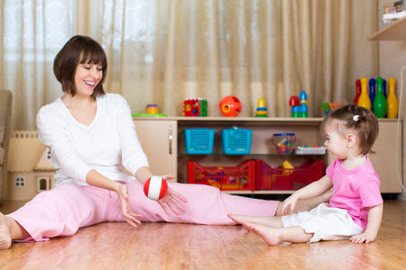 mother and kid play with toy ball indoors photo