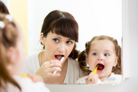 mother teaches child brushing teeth photo