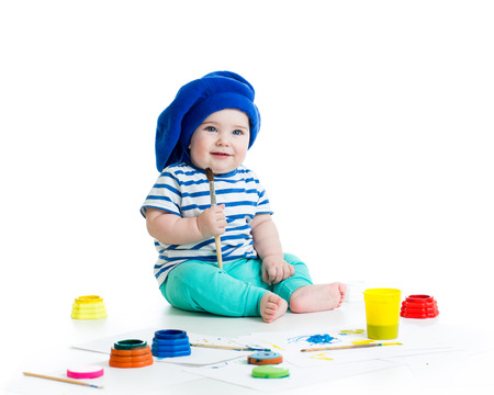 baby boy with paintbrush and paints photo