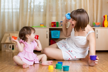 two floors: kid girl and mother playing together with cup toys Stock Photo
