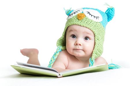 baby in grappige uil gebreide muts uil met boek op witte achtergrond Stockfoto