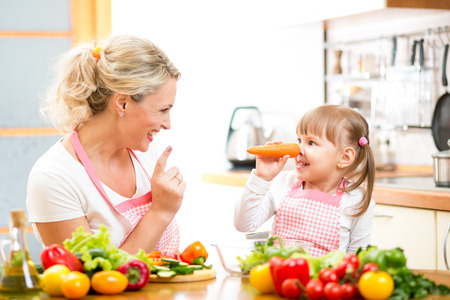 mother and child preparing healthy food and having fun photo