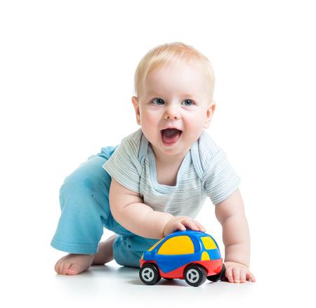 bebe gateando: niño chico divertido que juega con el coche del juguete