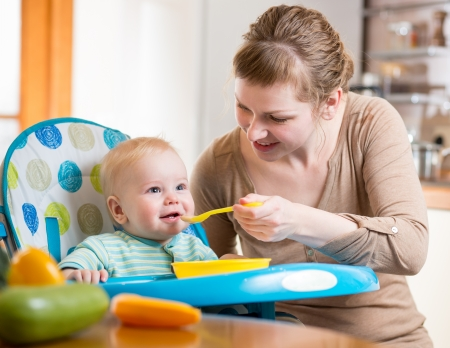 Mom feeds funny baby with spoon Stock Photo - 25088490