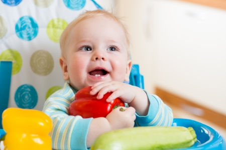 eats: baby with vegetables sitting in chair on kitchen