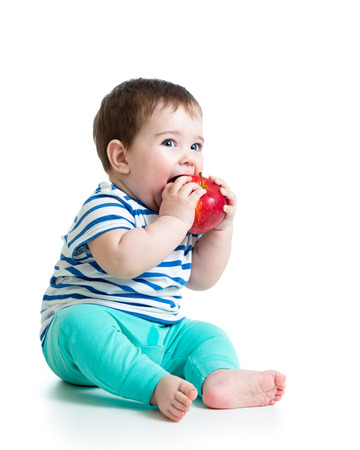 baby eating: Baby boy eating red apple, isolated on white