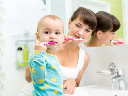 kid and mother brushing teeth photo