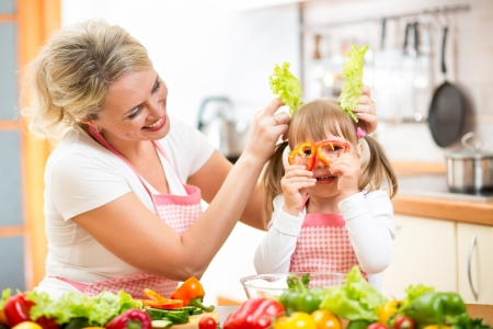 mother and kid cooking and having fun in kitchen photo