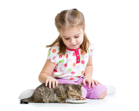 little girl feeding cat kitten photo