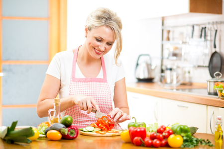 woman cooking: Cute woman cuts paprika for salad sitting at the kitchen table