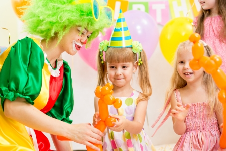 kids birthday party: jolly kids group and clown on birthday party Stock Photo