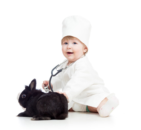 kid with clothes of doctor playing with pet bunny photo