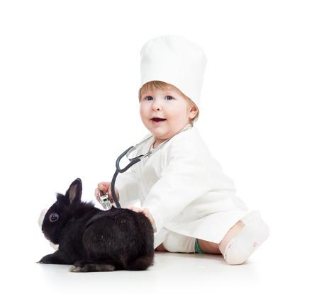 enfermera con cofia: niño con la ropa del doctor sonriente con el conejito mascota