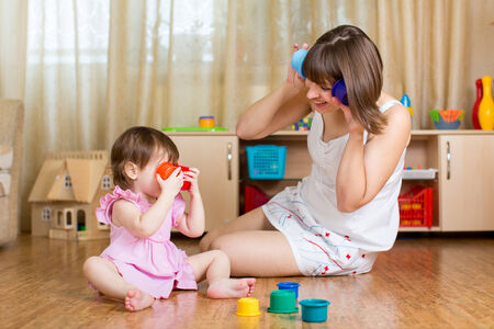 child and her mother playing together with toys photo