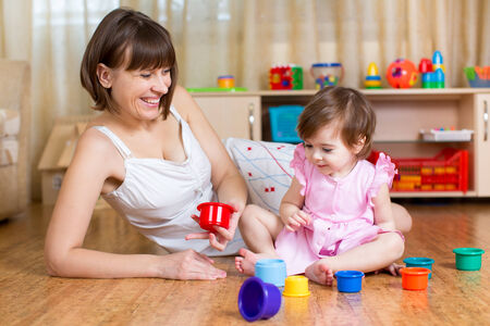 kid girl and mother playing together with colorful toys photo