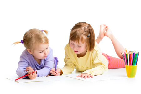 two girls drawing with color pencils together over white photo