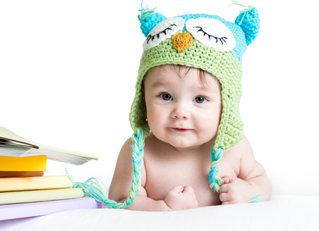 knit cap: baby in funny owl knitted  hat owl with books  on white background