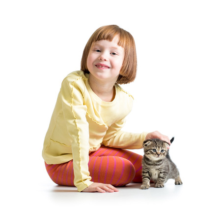 smiling child girl playing with cat kitten photo