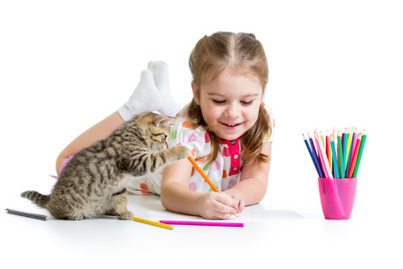 kid girl drawing with pencils and playing with kitten photo