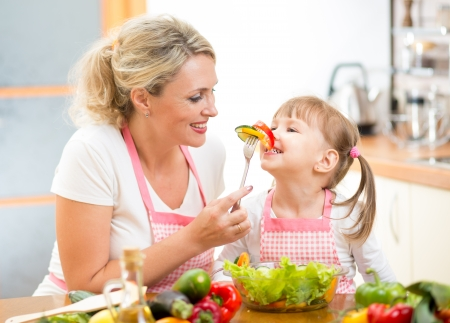 mother feeding kid daughter vegetables in kitchen photo