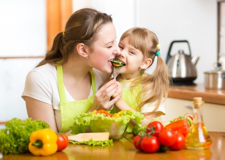mother feeding kid vegetables in kitchen Stock Photo