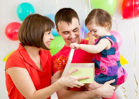 kid girl with parents opening gift box photo