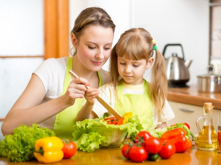 beautiful salad: mother teaching kid daughter mixing salad at kitchen Stock Photo