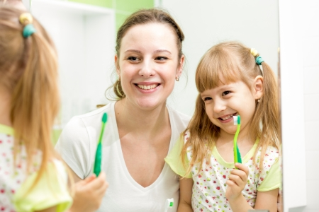 mother teaches kid brushing teeth photo