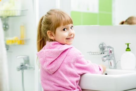 child girl washing her face and hands in bathroom photo