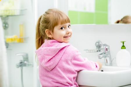manos limpias: niño de la muchacha que se lava la cara y las manos en el baño