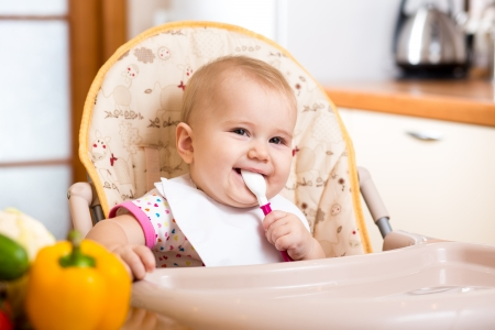 smiling baby eating food on kitchen photo
