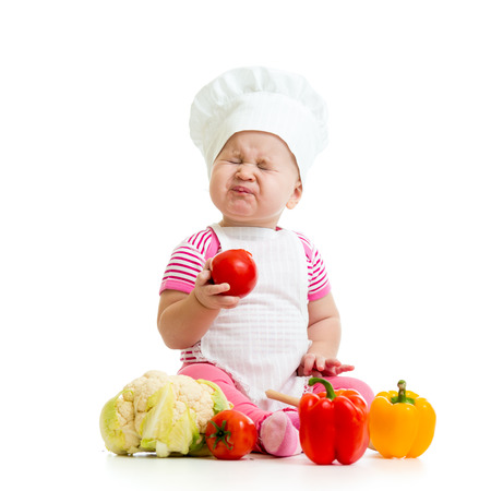 pucker: funny baby girl weared cook with vegetables Stock Photo